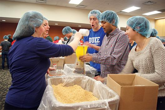 Students and community members volunteer during a past MLK Meal Packaging Event.