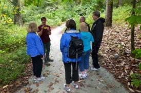 A tour guide leads a group through the Gardens, presenting to the group a yellow leaf.