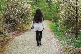 A woman walks down a path in Duke Gardens.