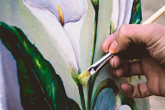 An artist paints a picture of a flower.