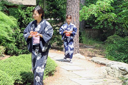 Japanese tea practitioners carrying bowls of tea.
