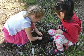 Two children dig into the soil.