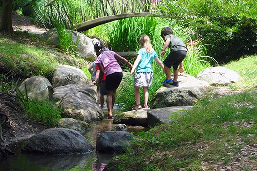 Children climb over rocks in a stream.