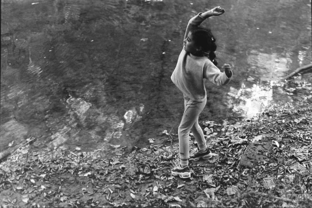 A young black girl at Eno River mid-throw.
