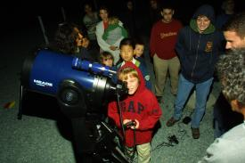 A boy operating telescope at Open House
