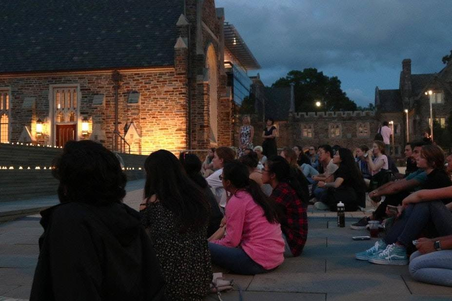 Image of students sitting outside of the Bryan Center Plaza waiting to hear student speakers; Candles placed on the stairs