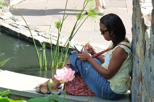 Teacher in Duke Gardens drawing by a fountain.