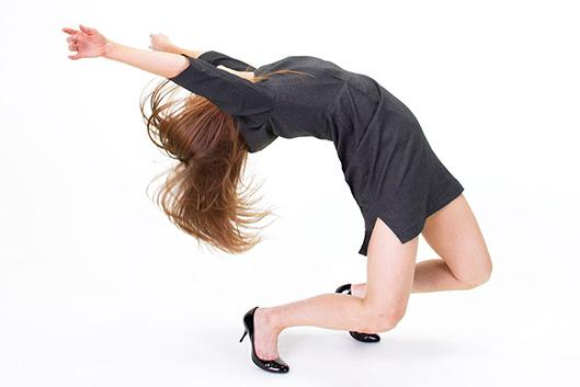 Woman throwing her body backwards modern dancing in professional work clothes.