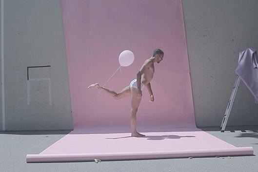 Man performing modern dance in a bathing suit against a pink background outside with a pink balloon tied to his foot.