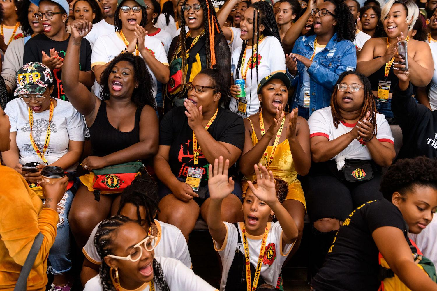 A group of black womxen cheer and clap at the Black Youth Project 100 National Convening. Photo taken by Christopher Jason.