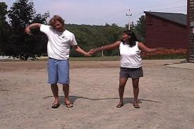A woman showing a man how to dance outside.
