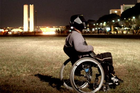 film still from White Out, Black In. Man in wheelchair wearing futuristic helmet.