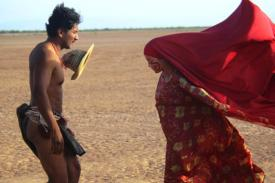 film still from Birds of Passage. Indigenous woman in red confronts man.