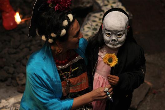 Film still for Two Fridas: woman and little girl in a skull mask