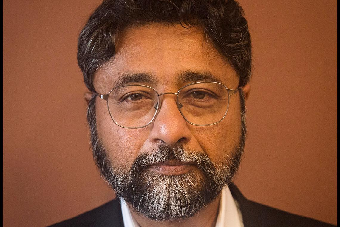 Anjan looks directly at the camera wearing a black suit and white button down. He wears glasses and has a full beard and mustache.