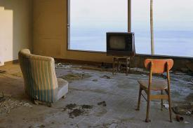 Two empty chairs face an old TV box. The window behind the TV shows the sea. Photo by Max Ernst Stockburger.