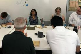 "Sneha Mantri sits in the middle of the table with 5 participants surrounding her as she talks about Narrative Medicine. The whiteboard behind her says, ""Welcome to a Narrative Medicine Workshop with neurolgist, Dr. Sneha Mantri."""
