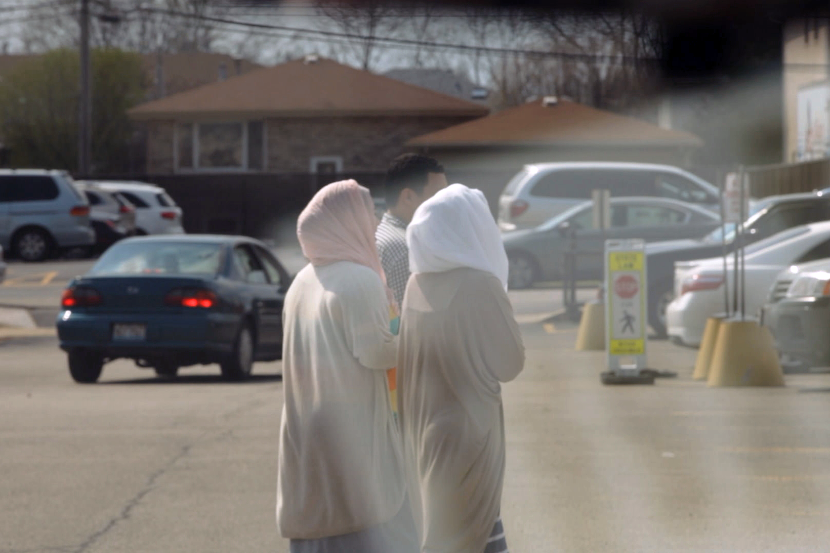 stillshot from the documentary featuring three people, two in hijab, and one man with short hair walking. the image is murky and taken from a distance, suggesting that it was taken from within a car