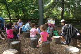 children listen to a story outdoors