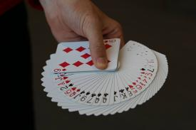 Hand holding playing cards showing all suites
