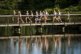 Duke runners on bridge reflected in water