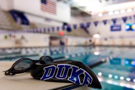 Duke swim cap and goggles on starting platform at edge of pool