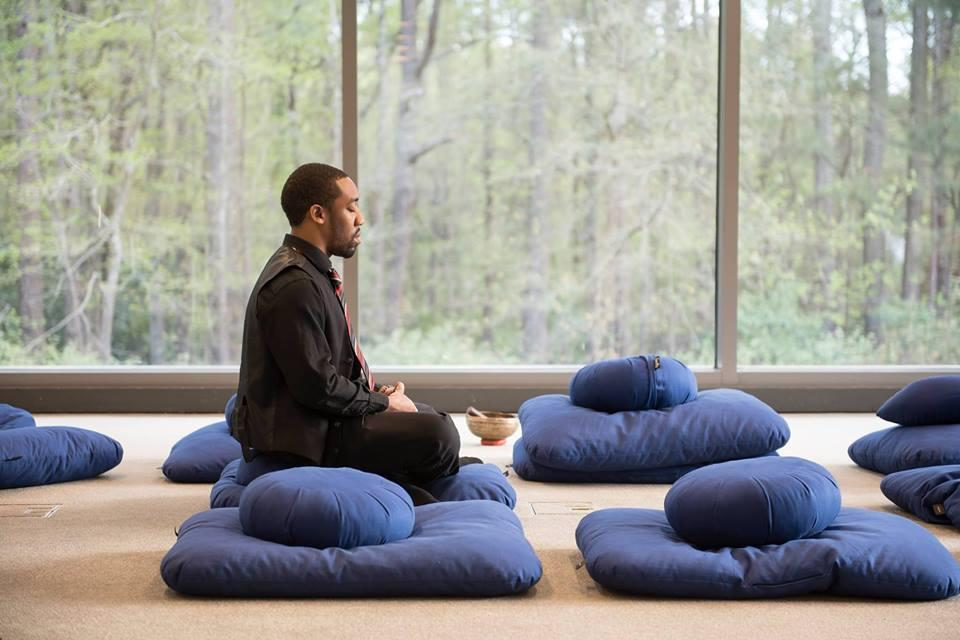 Man dressed in all black sitting on top of two meditation pillows while in a glass room that is surrounded by nature.