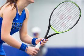 Duke tennis player holding racket