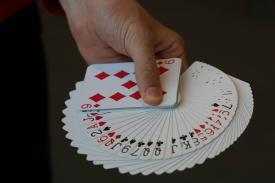 Hand holding a deck of cards facing up