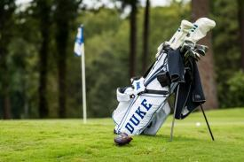 Duke golf bag adjacent to putting green