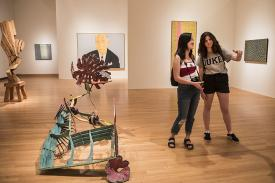 Students observing and discussing works of art presented in Disorderly Conduct: American Painting and Sculpture, 1960-1990