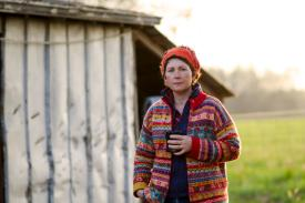 A woman holding a mug stands in front of a barn in Hillsborough, NC for a portrait photo.