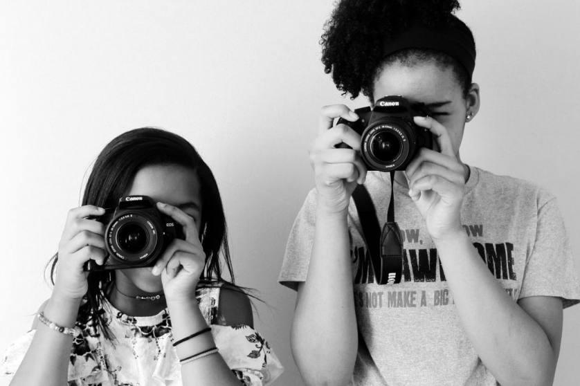 A black and white photo. Two young Black girls look through the viewfinder of Canon DSLRs, their faces obscured. They point their cameras at the viewers head-on.
