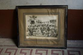 "A still image taken for Kamal Badhey's ""Family: Reinterpreting the Personal Archive"" fall course. A lone framed picture of a large group of people (presumably a family) is propped against the wall."