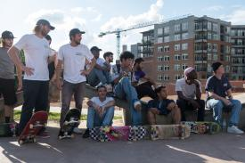 A group of skateboarders look off-camera to the right.