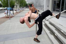 Man dancing with shirt off outside in downtown Raleigh on sidewalk wrapping his legs around a railing and leaning back.