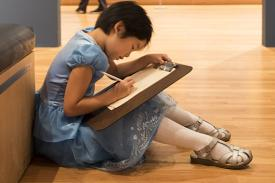 A child draws in the galleries at the Nasher Museum.