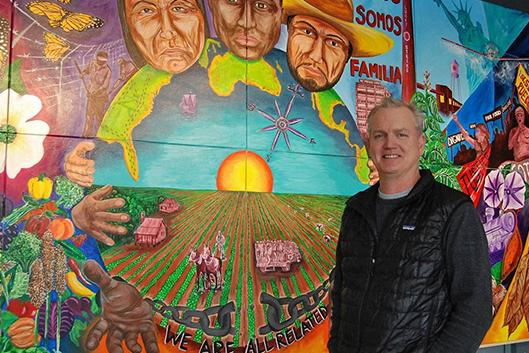 Bill Fick stands in front of the Rubenstein Arts Center's mural created by Duke students and Durham artist Cornelio Campos. Photo by Stephen Schramm.