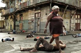 still from Invasión: woman stepping over bodies in the street