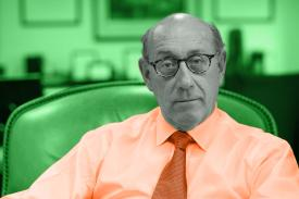 Picture of Kenneth Feinberg sitting in a chair. Green background, orange shirt, black and white face.