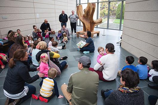 Families with children and babies listen to a story read in Spanish at the Museum