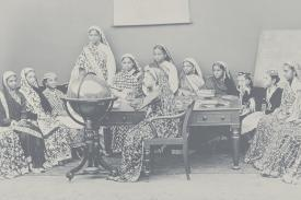 Picture of women in Indian dress looking at a globe in a classroom