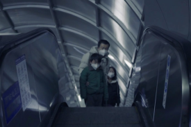 Male adult with two children, all wearing surgical masks, riding up escalator