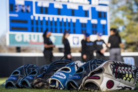 softball gloves in foreground, stadium and players out of focus