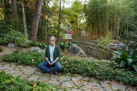 Betsy Dessauer meditates in the arboretum