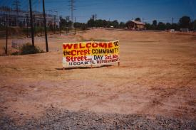 "A lone sign stands in an empty land. ""Welcome to the Crest Community Street,"" it says. A church stands in the background."
