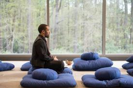 Man sitting on meditation pilliows.