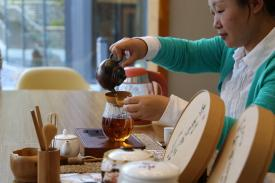 Person pouring tea into a tea cup with a full tea display in front of her
